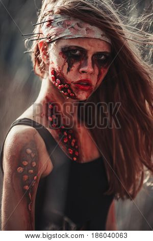 Mutant girl portrait in wounds and ulcers with nails in her head. On her head is bandage.