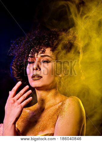 Golden powder cosmetics on bare woman shoulders with decorative. Girl with curls on dark background. Woman at disco In gold mystical fog .