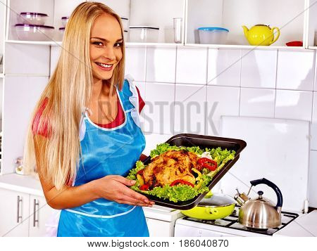 Woman in kitchen is cooking roast meat food in oven. Chicken is oven- tray with lettuce leaf. Housewife wearing apron in home interior preparing barbecue for friends. Girl wants to get job as cook.