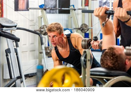 Friends in gym workout with fitness equipment. Man workout dumbbell at gym. Group people working on simulator body . Handsome guy foreground looks at camera. Preparation of athletes for competitions.