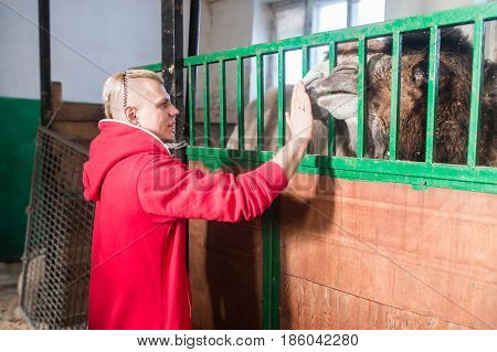 The trainer man in the circus stands in front of the cage with a camel in the paddock.