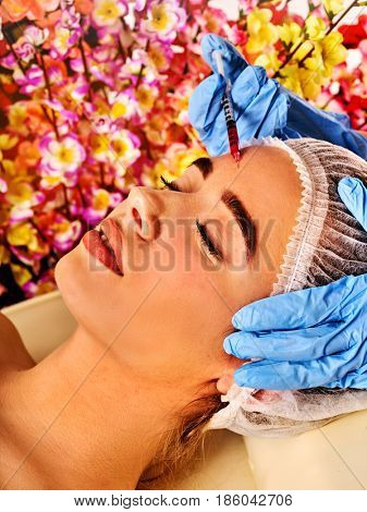 Filler injection for female forehead face. Plastic aesthetic facial surgery in beauty clinic. Beauty woman giving injections. Doctor in medical gloves with syringe on spring flowers background.