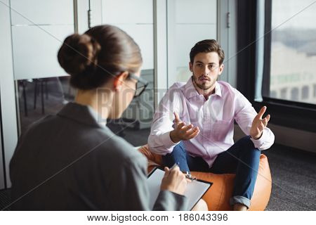 Counselor consoling unhappy man during therapy