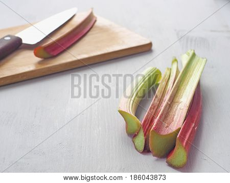 Cooking process. Home baking concept. Preparing rhubarb cake. Ripe rhubarb stems and some utensils  upon wooden board. Selective focus. Copy space for your text.