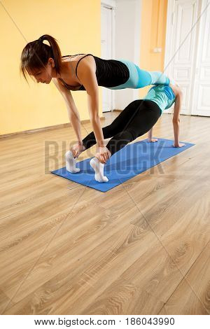 Two sports women practice yoga in gym