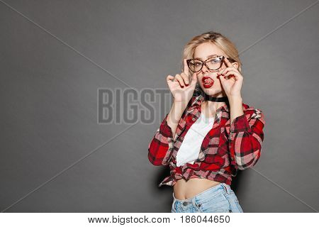 Pretty young hipster girl in casual clothing and glasses posing sensually on studio background.