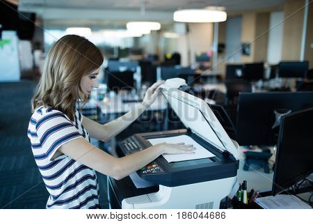 Side view of businesswoman using copy machine in office