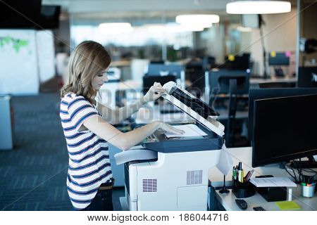 Side view of young businesswoman using copy machine in office
