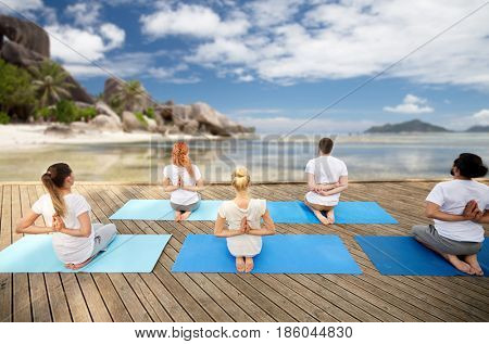 fitness, yoga, meditation and sport concept - group of people exercising in reverse prayer pose over exotic tropical beach background