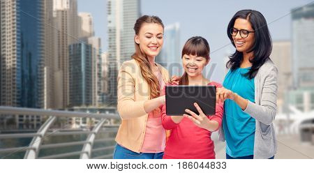 travel, tourism and people concept - international group of happy smiling different women with tablet pc computer over dubai city street background