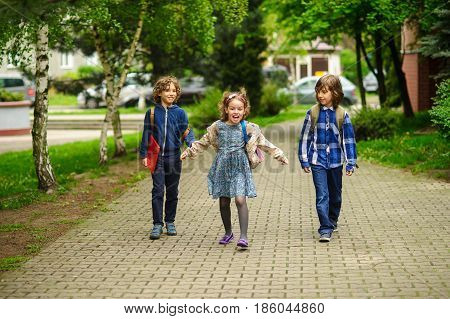 Amusing little school students go to school having joined hands. Children have an excellent mood. Behind shoulders schoolbags. Serene spring day.