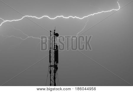 Antenna for a cellular connection under a thunderbolt (lightning attack) - night photo.