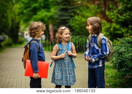 Cute little school students briskly talk on the schoolyard. Children have a good mood. Warm spring morning. Behind shoulders at schoolmates schoolbags. In hands of one of boys bright red folder.
