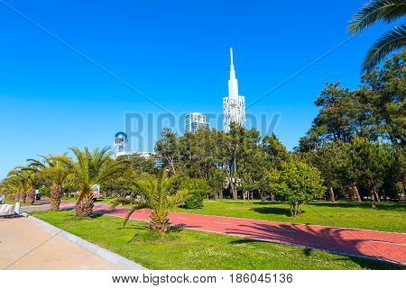 Park with palm trees near promenade of Batumi, Georgia and high modern houses