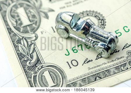 Little Car Made Of Chrome Is Laying On One Dollar Banknote,