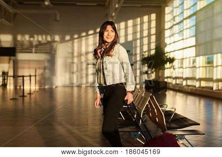 Woman smiling waiting her flight at airport terminal waiting room with her trolley bag.