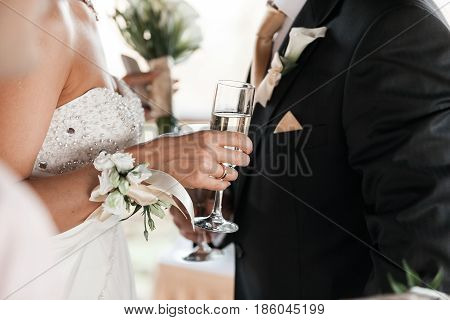 Happy newlyweds couple drink white wedding champagne wine.Decorated crystal glasses.Hands of bride and groom with gold ring toast with alcohol drinks.New family, husband and wife celebrate engagement.