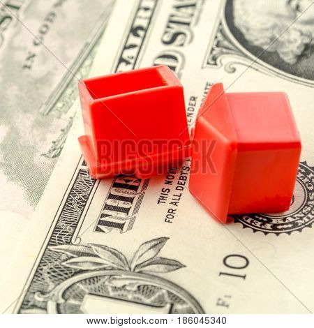 two little red houses made of plastic are laying on their roofs on dollar banknotes business concept