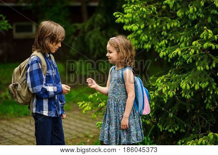 Two little school students the boy and the girl cheerfully communicate on the schoolyard. Behind shoulders at friends schoolbags. Against the background of magnificent spring greens.