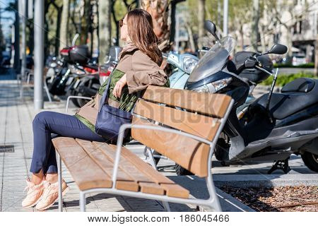 Woman at the street, sitting on bench. Barcelona, Catalonia.