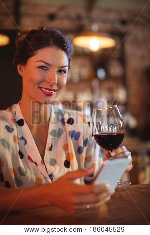 Portrait of young woman using mobile phone while having wine in pub
