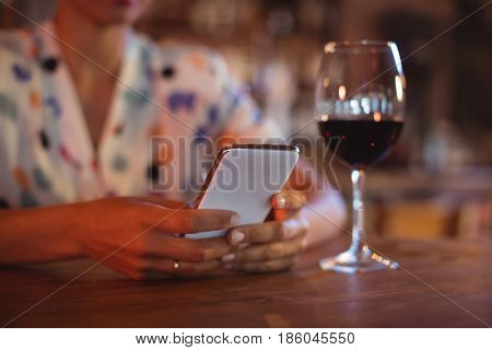 Mid-section of woman using mobile phone in pub