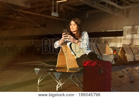 Casual young woman using her cell phone while waiting her flight at airport terminal waiting room.