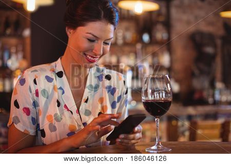 Young woman using mobile phone while having wine in pub