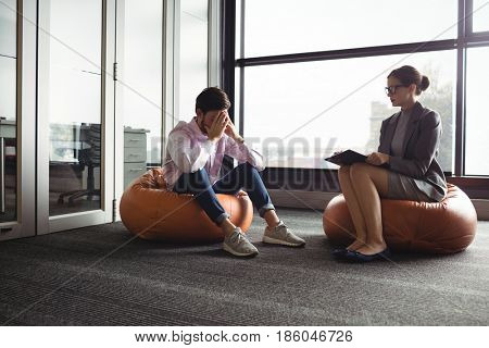 Unhappy man consulting counselor during therapy