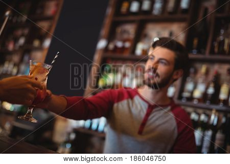 Female bar tender giving glass of cocktail to customer at bar counter