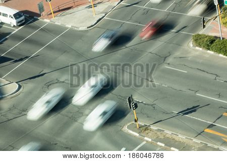 High angle view of blurred cars on road intersection during sunny day