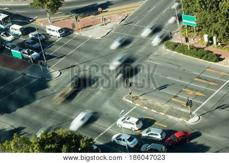 Blurred motion of cars on road intersection during sunny day