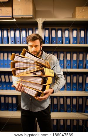 Worried businessman holding stack of files in storage room