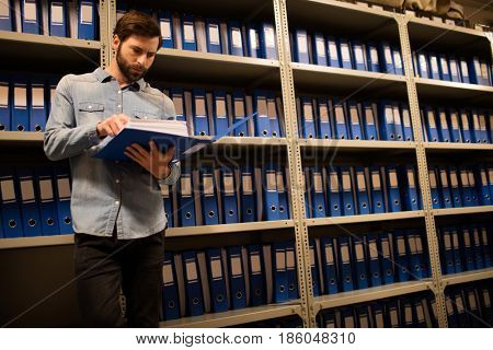 Concerned businessman reading file while standing in storage room