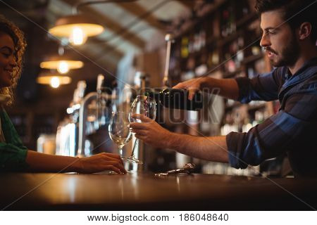 Male bar tender pouring wine in glasses at bar counter