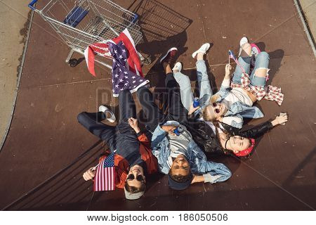 Elevated View Of Teenagers Having Fun And Lying With American Flag In Skateboard Park, Hipster Style