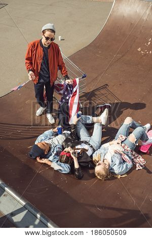 elevated view of teenagers having fun and lying with american flag in skateboard park hipster style concept