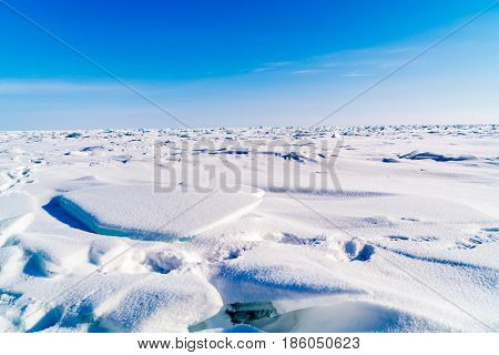 Field of blue frozen water covered with snow in Lake Baikal Russia during winter