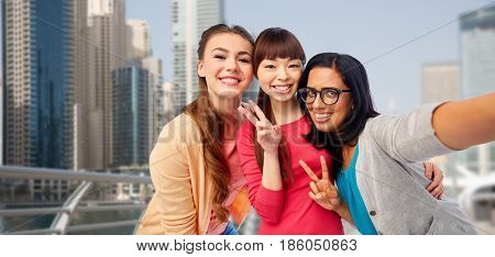 travel, tourism and people concept - international group of happy smiling different women taking selfie and showing peace hand sign over dubai city street background