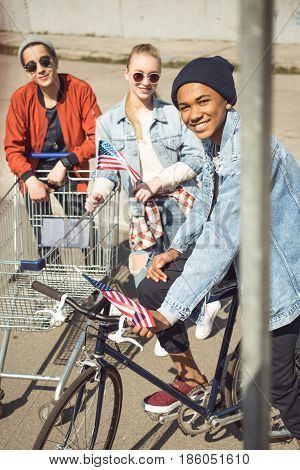 teenagers having fun with shopping cart and bicycle in skateboard park hipster students concept