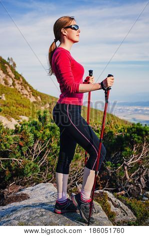 Young sport woman with poles standing at high mountains and looking aside