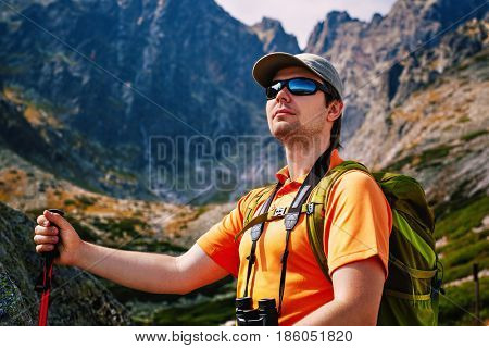 Young man tourist with green backpack and sunglasses portrait on high mountains background
