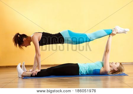 Two sports girls practice yoga in gym