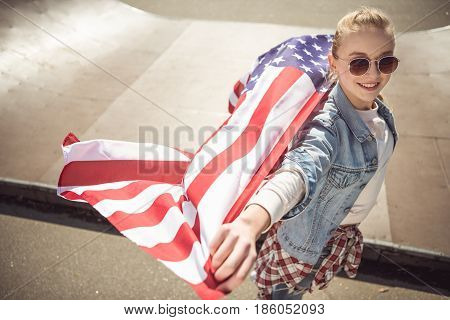 Young blonde girl holding american flag while standing on ramp at skateboard park