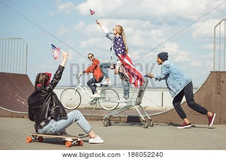 Teenagers Group With Skateboard, Bicycle And Shopping Cart Having Fun Together And Waving American F