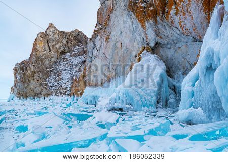 View of rocky island with icicles and ice blocks covered with snow in Frozen Lake Baikal Russia