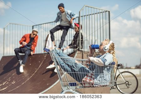 Girl In Headphones Sitting In Shopping Cart And Drinking From Can While Friends Having Fun On Ramp A