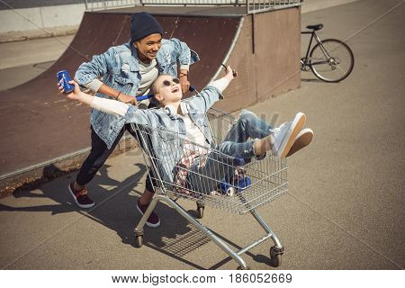 Boy carrying happy girl with can in shopping cart near ramp at skateboard park