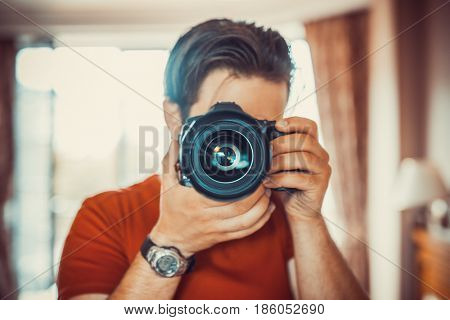Young man photographer making selfie at mirror. Focus on camera lens.