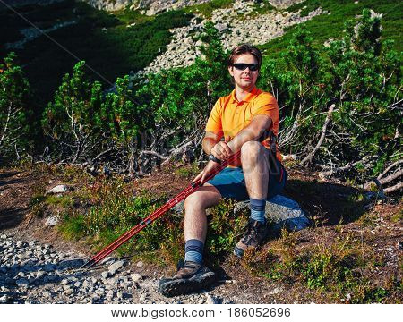 Young man tourist with sunglasses sitting at mountains portrait